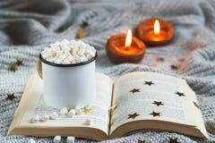 Weißer Becher mit Kakao und Eibisch auf einem offenen Buch auf einem hellgrauen strukturierten BAC stockfoto