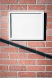Weißer Bilderrahmen auf Wand-Landschaftsvertikale des roten Backsteins Lizenzfreie Stockfotos