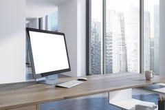 Weißer Bildschirm auf einer hölzernen Schreibtischseite Stockfoto
