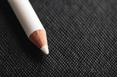 Weißer Bleistift für französische Maniküre auf einem schwarzen strukturierten Hintergrund Lizenzfreie Stockbilder