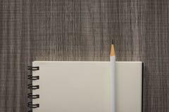 Weißer Bleistift mit leerem Notizbuch Stockbild