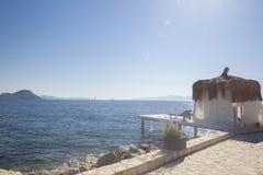 Weißer Bungalow mit einem Bambusdach und einem kleinen Pier mit einem Weiß Lizenzfreie Stockfotos