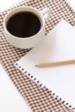 Weißer Cupkaffee mit Notizblock und Bleistift Stockfoto