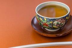 Weißer dämpfender Tee in der japanischen Schale auf dem braunen hölzernen Behälter Lizenzfreie Stockbilder