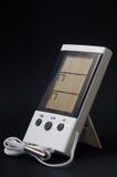 Weißer digitaler Thermometer mit einem Sensor auf einem schwarzen Hintergrund Stockbilder