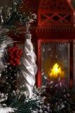 Weißer Eiszapfen, der an einer Niederlassung eines Weihnachtsbaums gegen eine rote Laterne mit einer Kerze hängt Stockbilder