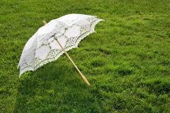 Weißer eleganter Regenschirm auf frischem Gras Stockbild