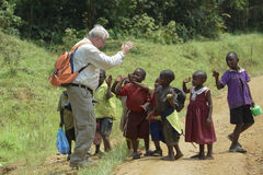 Weißer Europäer begrüßt afrikanische Kinder Stockbilder