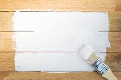 Weißer Farbenraum mit Malerpinsel auf hölzernem Hintergrund Stockfoto