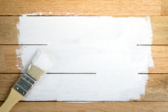 Weißer Farbenraum mit Malerpinsel auf hölzernem Hintergrund Stockfotos
