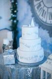 weißer Feiertagskuchen der Drei-Schicht auf dem Tisch verziert mit Tannenbäumen und Geschenkbox lizenzfreies stockbild