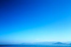 Weißer Felsen oder Kiesel in einem weißen sandigen Strand unter blauem bewölktem Himmel in einem falschen Wetter Lizenzfreie Stockbilder