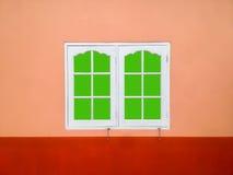 Weißer Fensterrahmen auf einer orange Wand, grüner Schirm mit Beschneidungspfad Lizenzfreies Stockfoto
