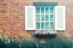 Weißer Fensterrahmen der Weinlese auf antiker Backsteinmauer mit Morgenli Stockfotografie