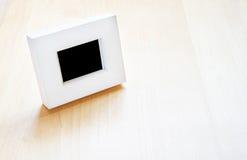Weißer Fotorahmen auf Holztisch, Schablonenspott oben für das Addieren von y Stockfotos