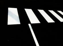 Weißer Fußgängerübergang auf schwarzem Teer Stockbilder