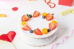 Weißer Geburtstagsfeierhintergrund mit gesundem yougurt Beerenkuchen, hellen Parteiwerkzeugen und Dekoration Glückliches Feiertag Stockfotografie