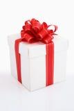 Weißer Geschenkkasten mit rotem Farbband Stockfotografie
