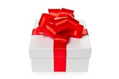Weißer Geschenkkasten mit rotem Satinbogen und -farbband Lizenzfreie Stockfotos