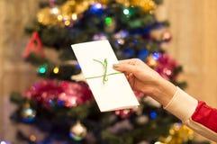 Weißer Geschenkumschlag in einer weiblichen Hand mit Weihnachtsbaum mit oder Lizenzfreies Stockfoto