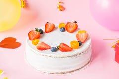 Weißer gesunder yougurt Beerenkuchen, helle Parteidekoration und Ballone auf hellrosa Parteihintergrund Glückliches Feiertagsdesi Stockbilder