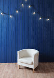 Weißer Gewebelehnsessel auf einem Hintergrund der blauen Wand mit Retro- Girlande von Glühlampen Beschaffenheit für den Entwurf Stockfotos