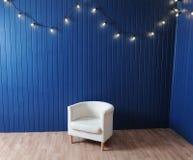 Weißer Gewebelehnsessel auf einem Hintergrund der blauen Wand mit Retro- Girlande von Glühlampen Beschaffenheit für den Entwurf Stockfotografie