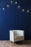 Weißer Gewebelehnsessel auf einem Hintergrund der blauen Wand mit Retro- Girlande von Glühlampen Beschaffenheit für den Entwurf Lizenzfreie Stockfotos