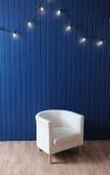 Weißer Gewebelehnsessel auf einem Hintergrund der blauen Wand mit Retro- Girlande von Glühlampen Beschaffenheit für den Entwurf Stockbilder
