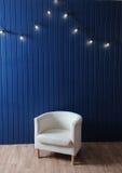 Weißer Gewebelehnsessel auf einem Hintergrund der blauen Wand mit Retro- Girlande von Glühlampen Beschaffenheit für den Entwurf Stockfoto