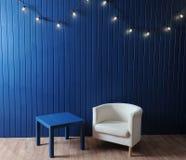 Weißer Gewebelehnsessel und blaue Tabelle auf einem Hintergrund der blauen Wand mit Retro- Girlande von Glühlampen Stockfotografie