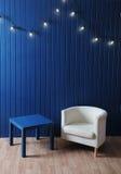 Weißer Gewebelehnsessel und blaue Tabelle auf einem Hintergrund der blauen Wand mit Retro- Girlande von Glühlampen Stockfoto