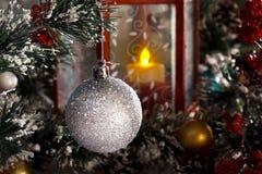 Weißer glänzender Ball, der an einer Niederlassung eines Weihnachtsbaums gegen eine rote Laterne mit einer Kerze hängt Stockfotos