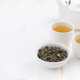 Weißer hölzerner Hintergrund mit Teekanne und Schalen grünem Tee Stockbild