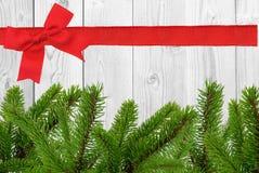 Weißer hölzerner Schreibtisch und roter Bogen, Band und grüner Weihnachtsbaum Stockbilder