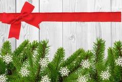 Weißer hölzerner Schreibtisch und roter Bogen, Band und grüner Weihnachtsbaum Stockfotografie