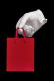 Weißer Handschuh, der rote Einkaufstasche anhält Lizenzfreie Stockfotografie