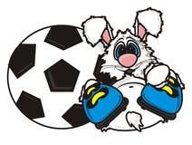 Weißer Hase liegt in den Stiefeln nahe einem Fußball Stockfotografie