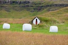 Weißer Hay Rolls auf einem grünen Feld von Island Lizenzfreie Stockbilder