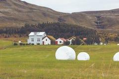 Weißer Hay Rolls auf einem grünen Feld von Island Stockbilder