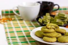 Weißer Hintergrund mit einem japanischen Bonbon, gemacht mit matcha und Schalen grünem Tee Lizenzfreies Stockfoto