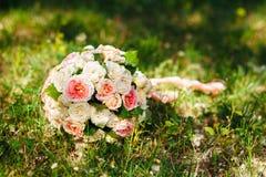 Weißer Hochzeitsblumenstrauß, der auf grünem Gras liegt Stockfoto