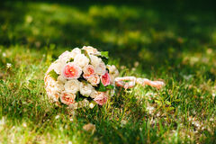 Weißer Hochzeitsblumenstrauß, der auf grünem Gras liegt Stockfotos