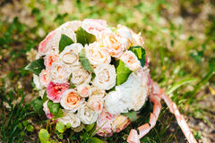 Weißer Hochzeitsblumenstrauß, der auf grünem Gras liegt Lizenzfreie Stockfotos