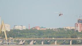 Weißer Hubschrauber fliegt über einen Fluss vor dem hintergrund der Stadt stock video