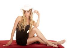 Weißer Hut der schwarzen Vertuschung der Frau sitzen auf dem roten Schauen Stockfotografie