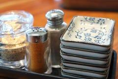 Weißer indischer Sesam in der Glasflasche mit Paprika- und Pfefferschüttel-apparat Lizenzfreies Stockfoto