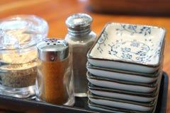 Weißer indischer Sesam in der Glasflasche mit Paprika- und Pfefferschüttel-apparat Stockfotos