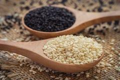 Weißer indischer Sesam und schwarzer Samen des indischen Sesams auf hölzernem Löffel Stockfotos