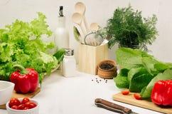 Weißer Innenraum der Küche mit rohem frischem grünem Salat, rote Kirschtomaten, Küchengeschirr auf weicher weißer hölzerner Tabel lizenzfreies stockbild